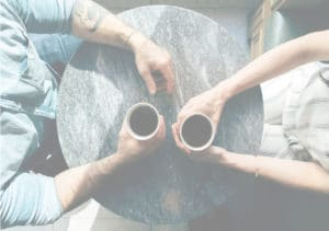 2 people having a coaching session over a cup of coffee